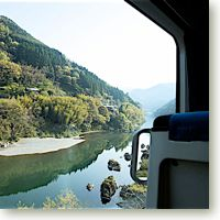 Shikoku mountains reflect in a river as seen from your train.